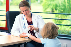 Female doctor bandaging the arm of a little girl Royalty Free Stock Image