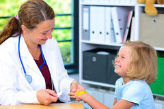 Female doctor bandaging the hand of a little girl Royalty Free Stock Photography