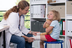 Female doctor bandaging the leg from a of girl Royalty Free Stock Image