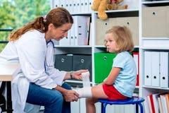 Female doctor bandaging the leg from a of girl. Female pediatrician in white lab coat bandaging the leg of a little girl Stock Images