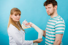 Female doctor bandaging male hand. Royalty Free Stock Photos
