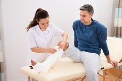 Female doctor bandaging patient's leg Stock Photography