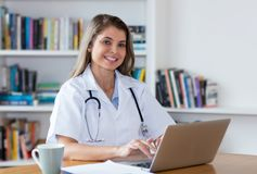 Female doctor with blond hair and computer looking at camera. At hospital stock photos