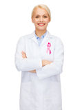 Female doctor with breast cancer awareness ribbon Royalty Free Stock Photography