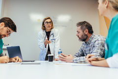 Female doctor briefing her colleagues in boardroom. Woman empowerment. Female doctor leading a meeting with her staff in boardroom. Woman medical professional Stock Images