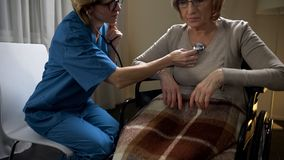Female doctor on call examining patient in wheelchair at home, medical reform royalty free stock image