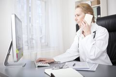 Female Doctor Calling Phone While Using Computer. Serious Adult Female Doctor Sitting at her Desk While Calling to Someone Over the Phone and Using her Desktop Royalty Free Stock Image