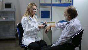 Cardiologist measuring patient`s blood pressure stock video