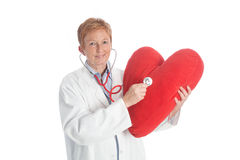 Female doctor of cardiology 1. Portrait of an elder female doctor of cardiology holding a red heart and red stethoscope, wearing a white lab coat, explaining Stock Images