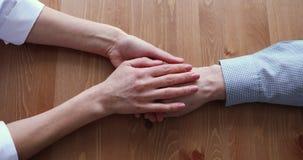 Female doctor caregiver stroking wrinkled hand of old man.