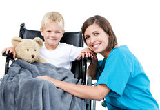 Female doctor carrying adorable boy. Nice female doctor carrying adorable little boy with his teddy bear in the wheelchair at the hospital Stock Photo