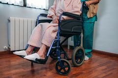 Doctor carrying elderly patient in a wheelchair. Female doctor carrying elderly female patient in a wheelchair Royalty Free Stock Image