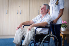 Female doctor carrying senior man on wheelchair Stock Images