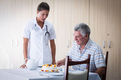 Female doctor celebration seniors man birthday in living room Royalty Free Stock Photos