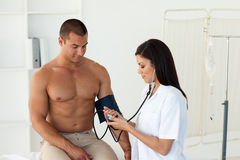 Female doctor checking the blood pressure Stock Photo