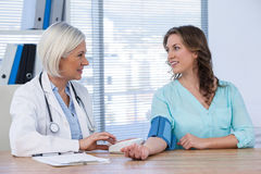 Female doctor checking blood pressure of a patient Stock Images