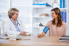 Female doctor checking blood pressure of a patient. In the hospital Royalty Free Stock Image