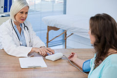 Female doctor checking blood pressure of a patient Royalty Free Stock Images