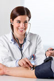 Female Doctor Checking Blood Pressure Of Patient. Portrait Of A Smiling Female Doctor Checking Blood Pressure Of Male Senior Patient Royalty Free Stock Image