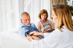 Female doctor checking blood pressure of senior man. Young female doctor checking blood pressure of senior man. Senior women holding tablet Royalty Free Stock Photos