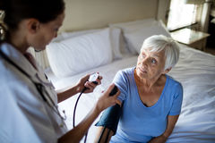 Female doctor checking the blood pressure of senior woman in the bedroom. At home Royalty Free Stock Image