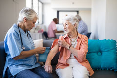 Female doctor checking blood pressure of senior woman. Female doctor checking blood pressure of senior women while sitting on sofa in nursing home Stock Photos