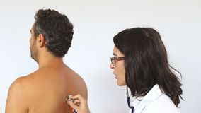 Female doctor checking a coughing patient stock footage