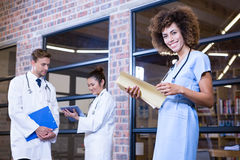 Female doctor checking a file near library Royalty Free Stock Photos