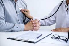 Female doctor checking heart beat of patient and recommend treat. Ment methods and how to use medicine stock photo