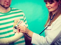 Female doctor checking heart beating. Corruption in medicine. Female doctor with stethoscope checking heart beating. Male bandaged hand with banknotes euro royalty free stock photos