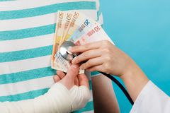 Female doctor checking heart beating. Corruption in medicine. Female doctor with stethoscope checking heart beating. Male bandaged hand with banknotes euro money royalty free stock image