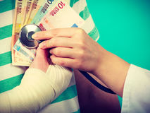 Female doctor checking heart beating. Corruption in medicine. Female doctor with stethoscope checking heart beating. Male bandaged hand with banknotes euro stock images