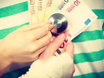 Female doctor checking heart beating. Corruption in medicine. Female doctor with stethoscope checking heart beating. Male bandaged hand with banknotes euro royalty free stock image