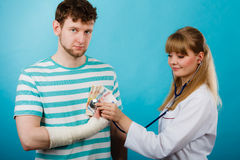 Female doctor checking heart beating. Corruption in medicine. Female doctor with stethoscope checking heart beating. Male bandaged hand with banknotes euro stock photos