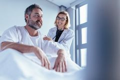 Female doctor checking male patient in hospital room. Female doctor checking male patient. Doctor visiting and talking with patient sitting in a hospital bed Royalty Free Stock Image