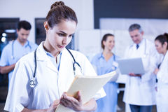 Female doctor checking a medical report. And colleagues standing behind Royalty Free Stock Photo