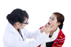 Female doctor checking patient health. Female doctor checking her patient by asking her to open her mouth Stock Photo