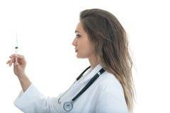 Female doctor checking a syringe isolated on white background Royalty Free Stock Images