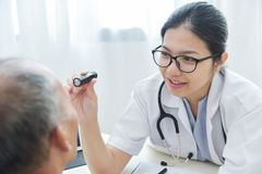 Female Doctor checking to senior man patient eyes. stock images