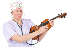 Female doctor checking violin with funny grimace Royalty Free Stock Photography