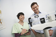Female Doctor Checking Weight Of Patient Royalty Free Stock Photos