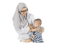 Female doctor checks baby on studio Stock Image