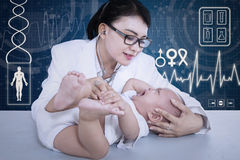 Female doctor checkup crying baby on blue digital Stock Photography