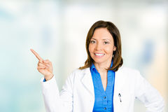 Female doctor cheerful healthcare professional pointing away Stock Photo
