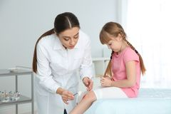 Female doctor cleaning little girl`s leg injury in clinic. royalty free stock photo