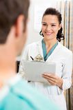 Female Doctor With Clipboard Looking At Patient Stock Images