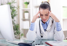 Female doctor with closed eyes sitting at the table and holding Stock Photography