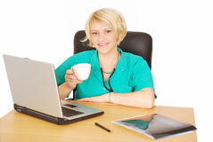 Female doctor with coffee and laptop Stock Images