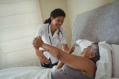 Female doctor comforting senior woman on bed. Female doctor comforting senior women on bed at home Royalty Free Stock Photos