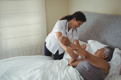 Female doctor comforting senior woman on bed Stock Photo